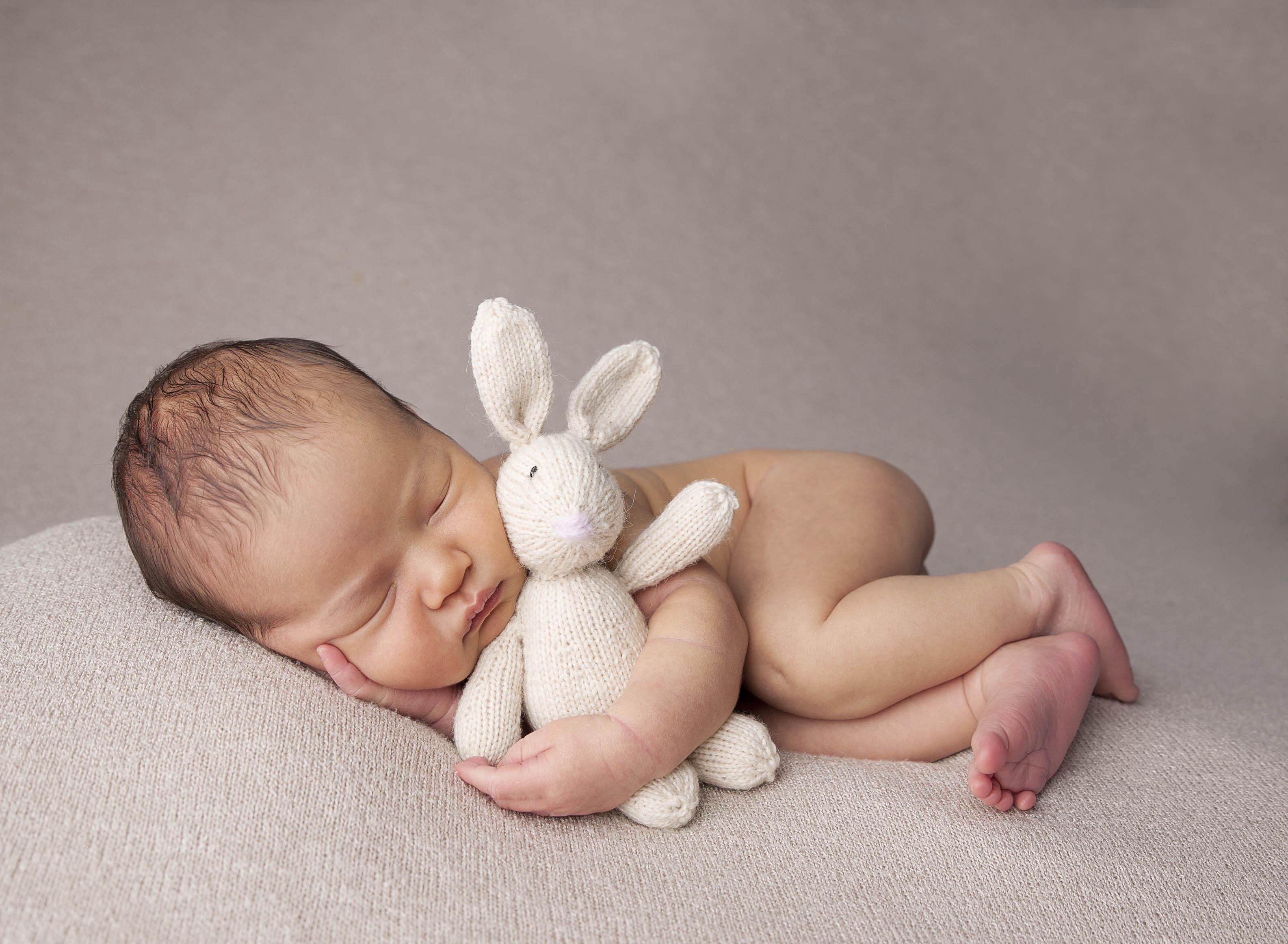baby holding stuffy comox